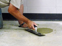 Repairing the cored holes in the concrete slab floor with fresh concrete and cleaning up the Riverton home.
