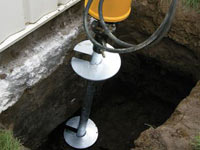 Installing a helical pier system in the earth around a foundation in Laramie
