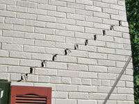 Stair-step cracks showing in a home foundation in Newcastle