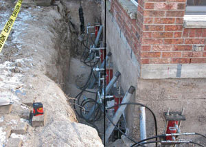 Foundation push piers installed around a house with a foundation settlement issues in Parkman